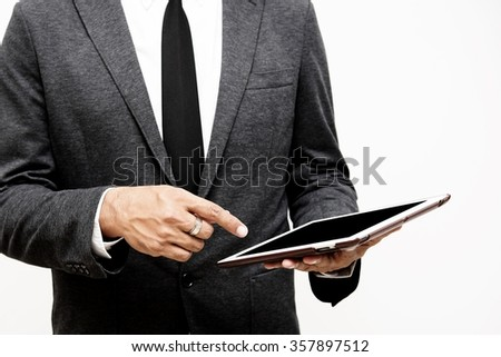 business man holding computer tablet selective focus on pointing finger - stock photo
