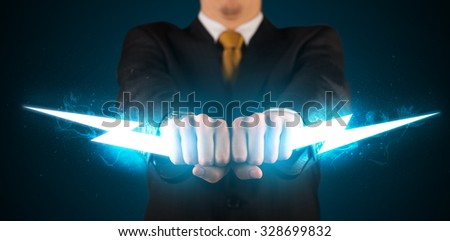 Business man holding glowing lightning bolt in his hands concept - stock photo