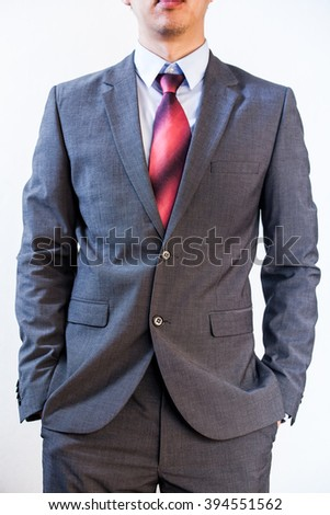 Business man holding his hands in pocket on white isolated background - stock photo