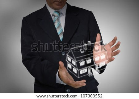 Business Man holding house or home - stock photo