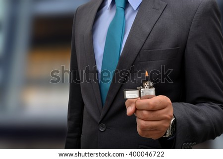 business man holding lighter in hand