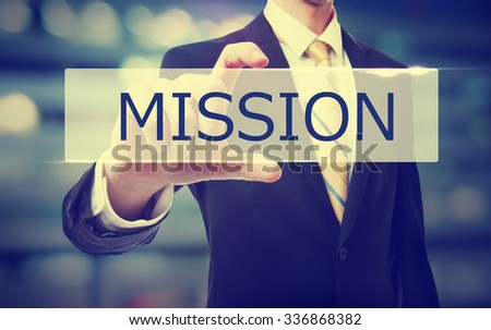 Business man holding Mission on blurred abstract background   - stock photo