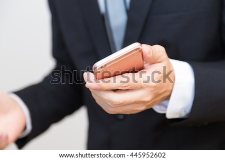 Business man holding mobile smartphone in to camera wear black professional suit