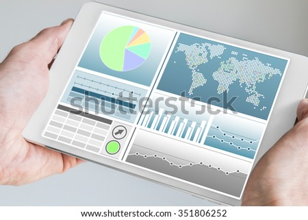 Business man holding modern tablet with both hands with business dashboard in neutral color - stock photo