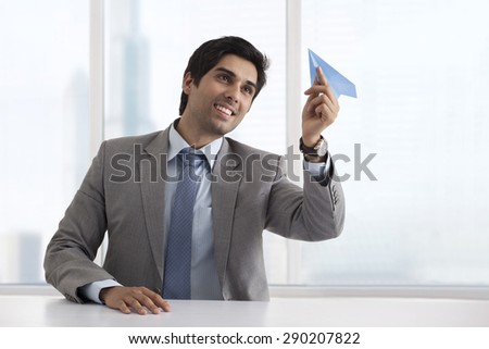 Business man holding paper airplane - stock photo