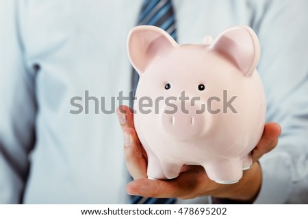 Business man holding piggy bank in hand. Savings and invest concept