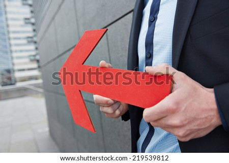 Business man holding red arrow to the left in the city - stock photo