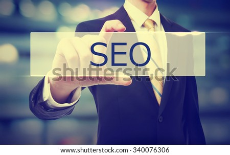 Business man holding SEO on blurred abstract background   - stock photo