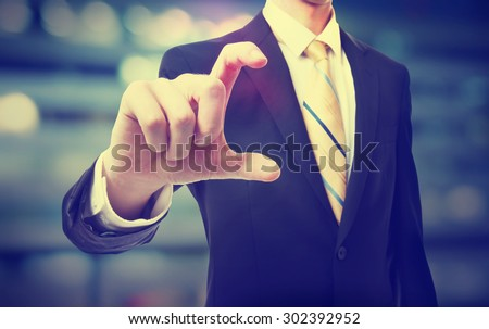 Business man holding something between his fingers on blurred cityscape background  - stock photo