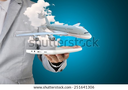 Business man holding tablet present airplane in his hand as transportation or travel concept - stock photo