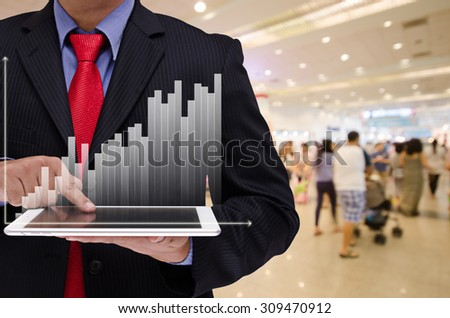 business man holding tablet with business graph virtual screen