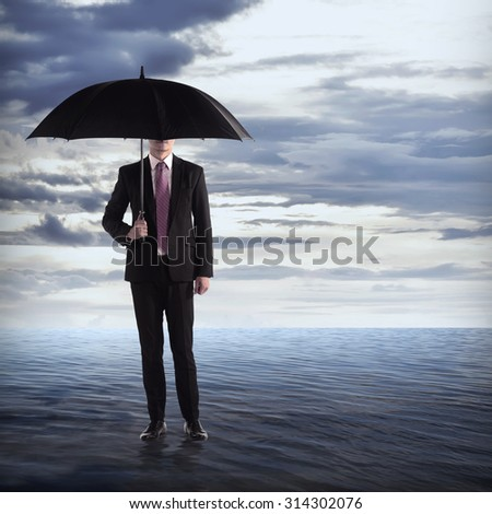 Business man holding umbrella in the middle of the ocean - stock photo