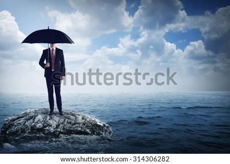 Business man holding umbrella on a rock in the middle of the ocean