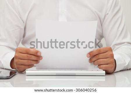 Business man holds blank sheet of paper in hands - stock photo