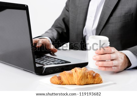 Business man holds coffee while working at desk with breakfast croissant, selective focus on hand - stock photo