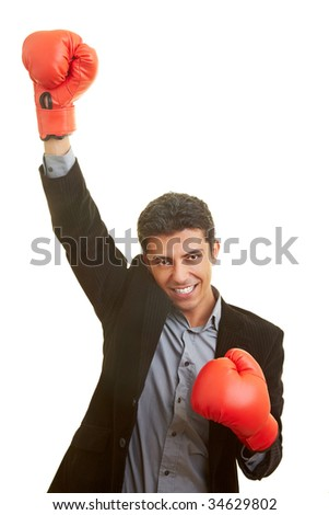 Business man holds up his hand with red boxing gloves - stock photo