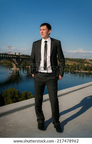 business man in a blue shirt against the blue sky - stock photo