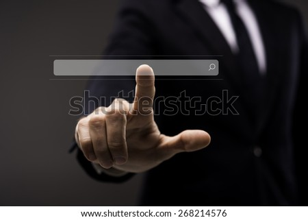 Business man in black suit touching imaginary screen with search button