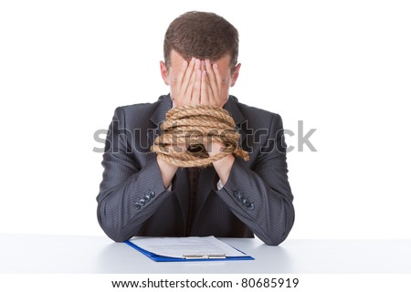 Business man in elegant suit sitting at desk tied hands cover face by hands with rope concept. Isolated over white background. - stock photo