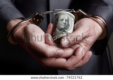 Business man in handcuffs arrested for bribe - stock photo