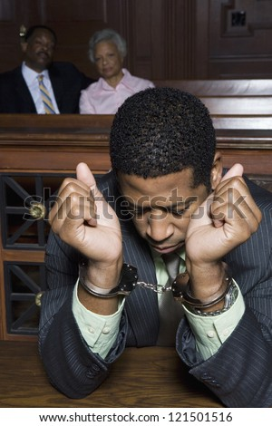 Business man in handcuffs in courtroom with two people looking at him - stock photo
