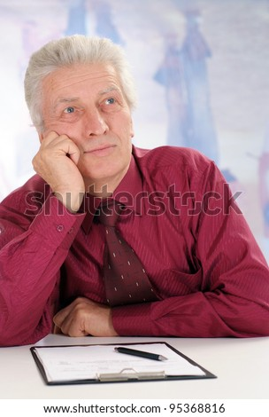 business man in maroon shirt sits on a white