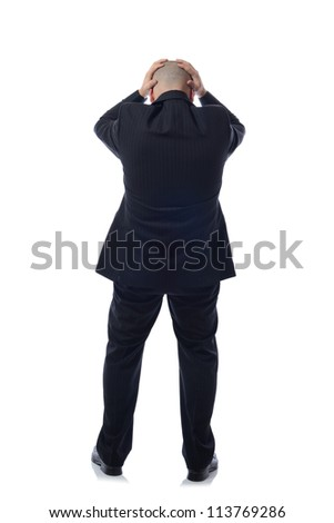 business man in modern elegant suit standing back holding head with his hands, isolated over white background. Concept of neck or head ache, pain, problem, tired up.
