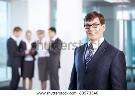 Business man in office compared to other staff - stock photo