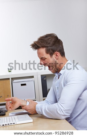Business man in office holding his aching mouse arm hand - stock photo