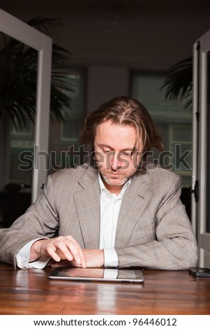Business man in office working with tablet. Light suit long hair. - stock photo