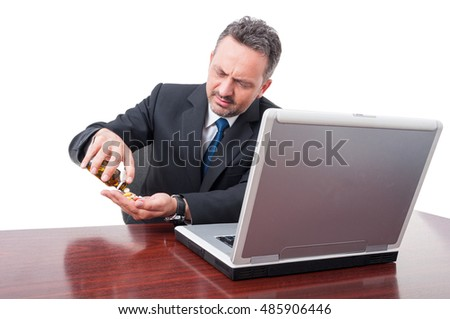 Business man in suit at office looking stressed and taking pills isolated on white background