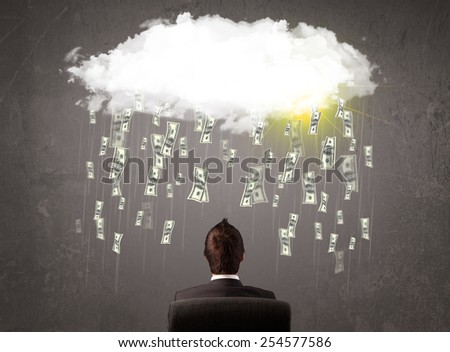 Business man in suit looking at cloud with falling money and sun - stock photo