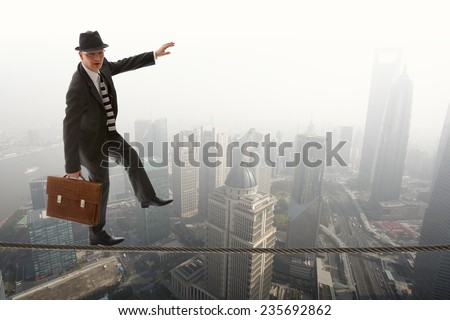business man in suit performing a tightrope act over the Shanghai skyline - stock photo