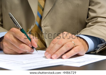 Business man in suit signing a contract or document - stock photo