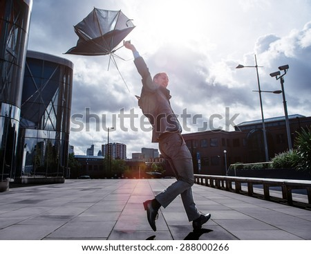 Business Man in the City with umbrella on stormy day - stock photo