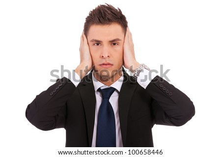 business man in the Hear no evil pose on white background. young businessman covering his ears with his hand - stock photo