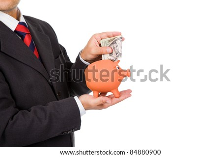 Business man inserting money into a piggy moneybox. Many space to write text on copyspace - stock photo
