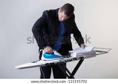 business man ironing out paperwork, keeping good documentations - stock photo