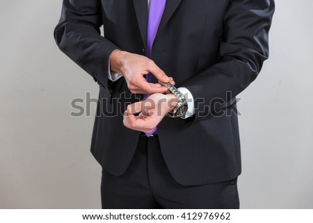 Business man is closing his wrist watch