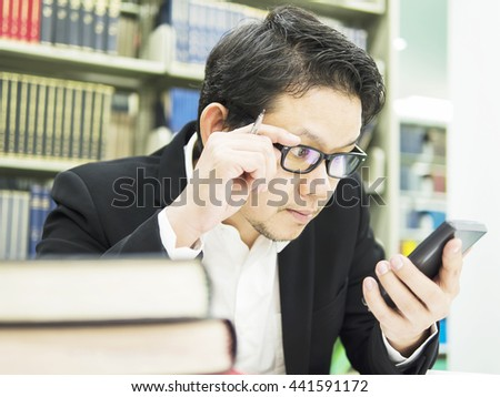 Business man is looking at his mobile phone in his office