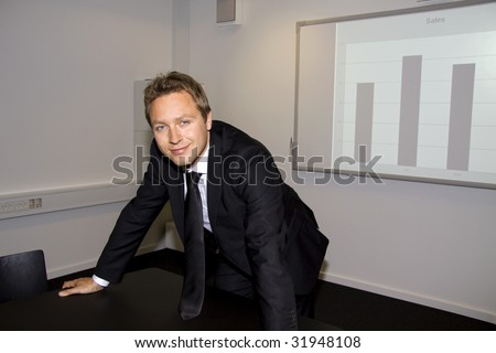 Business man is standing at the end of the table presenting the sales figures