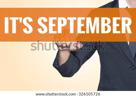 Business man It September word touch on virtual screen orange background - stock photo