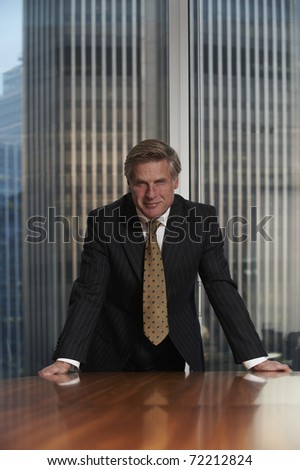 Business man leaning on chair in boardroom looking at camera