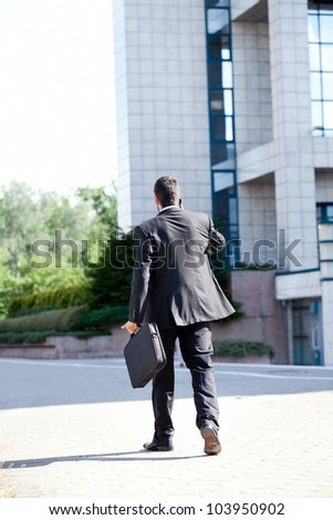 Business man leaving after a working day , end of a business day, back view - stock photo