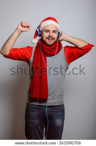 Business man listening to music with big headphones to the phone. Corporate party, Christmas hat isolated portrait of a man on a gray background, studio photo. - stock photo