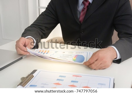 Business man look at growth paper in meeting room. Business plan and profit.