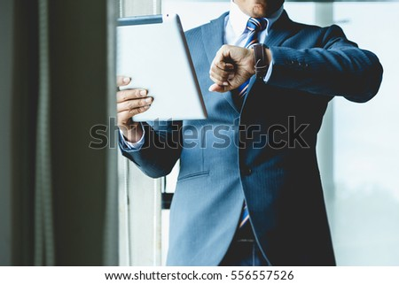 Business man looking at a clock in his office.