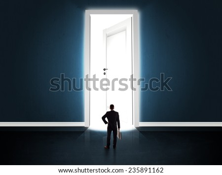 Business man looking at big bright opened door concept - stock photo
