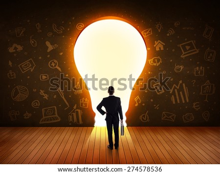 Business man looking at bright light bulb in the wall concept - stock photo