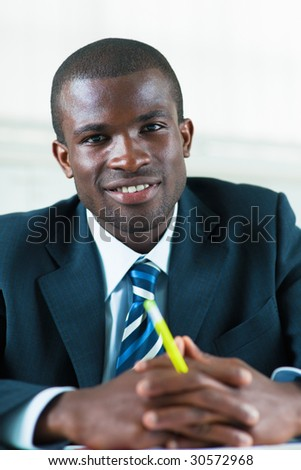 business man looking at camera with hands clasped - stock photo